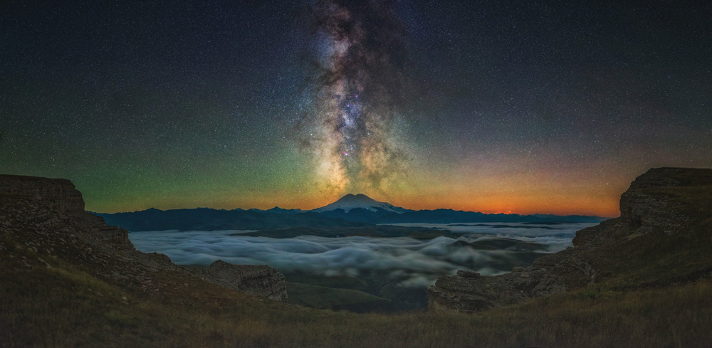 """In 2014, this picture won first place in the National Geographic Russia Wild Nature contest. Elbrus is a sleeping volcano and, at 5,642 metres, the highest peak in Europe. The picture has everything: placer stars, a giant volcano, mountains, and a blanket of clouds. In the foreground the southern tip of the Kanzhol plateau, the moon, which has come just behind the mountains, and the Milky Way as if escaping from the top of Mount Elbrus. I have this picture hanging on the wall in my house, and each time I look at it I find myself there, steeped in the moment. That's the true magic of photography."""